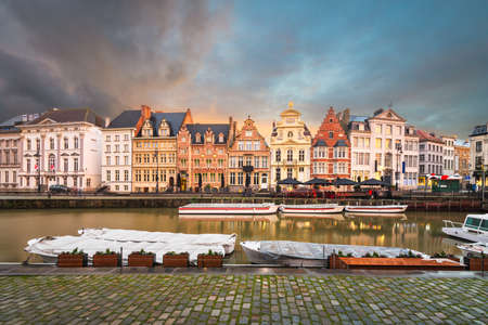 Ghent, Belgium old town cityscape and riverboats from the Graslei at twilight.