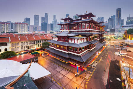 Singapore skyline with the Buddha Tooth Relic Temple at twilight.
