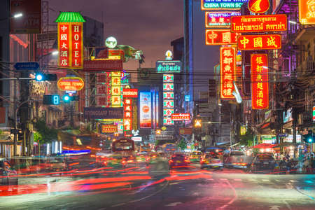 BANGKOK, THAILAND - SEPTEMBER 27, 2015: Traffic on Yaowarat Road passes below lit signs in the Chinatown district at dusk. Editöryel