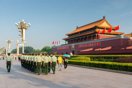 BEIJING, CHINA - JUNE 24, 2014: Soldiers March past tourists in front of The Tiananmen Gate.