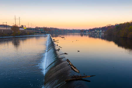 Philadelphia, Pennsylvania, USA dam on the Schuylkill River with Boathouse Row in the distance at dawn.