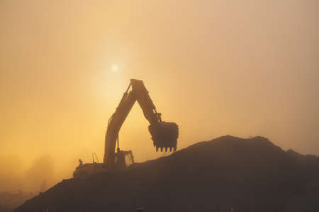 An excavator performs work in rubble in hazy and dusty early morning conditions.
