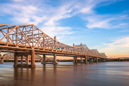 Louisville, Kentucky, USA with John F. Kennedy Memorial Bridge spanning the Ohio River at dusk.