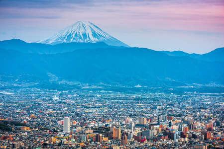 Kofu, Japan skyline with Mt. Fuji at dusk.