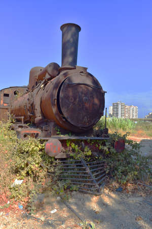 head of a rusty steam locomotive on an abandoned driway surrounded by vegetation, in Tripoli, Lebanon