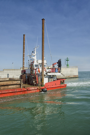 dredger: View of a dredger coming into harbor