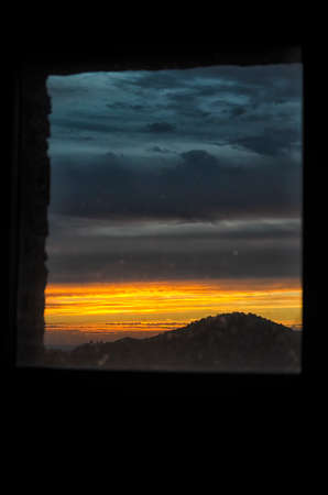 sunup: View of a sunrise squared by window