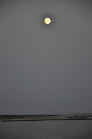 capo: View of the moon over the island of Capo Passero