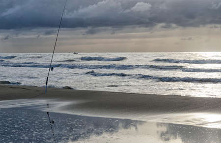 Fishing pole: Solitary fishing pole in the beach at sundown