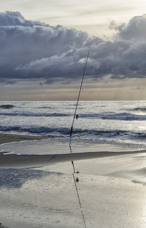 Fishing pole: Solitary fishing pole in the beach at sunset