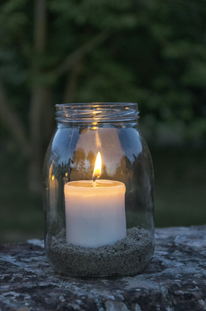 View of glass jar with lit candle inside