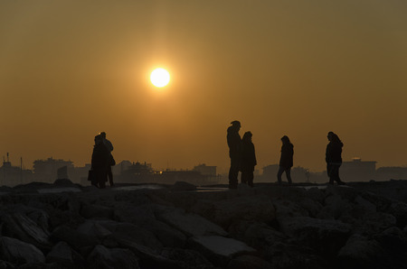 evocative: View of people watching an amazing sunset