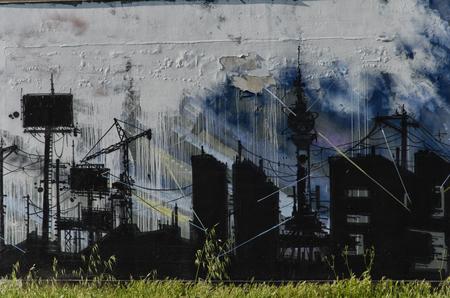 Weergave van een muurschildering met een somber industrieel landschap