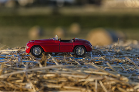 View of a luxury car on a straw round bale Editorial