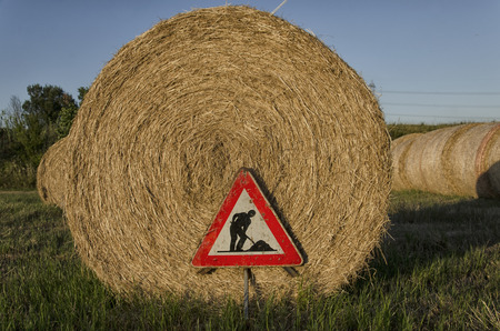 View of under construction roadsign over straw round bale