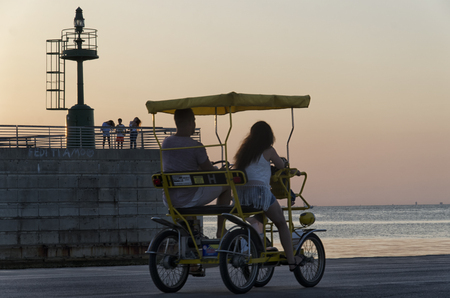 evocative: Rimini, Italy - July 31, 2017: Four-wheeled bicycle at the marina at sunset Editorial