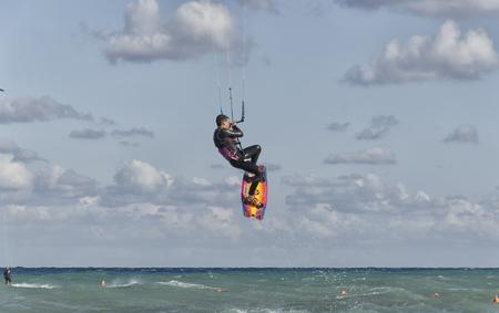Cesine, Italy - September 21, 2017: Kitesurfer while making an acrobatic leap