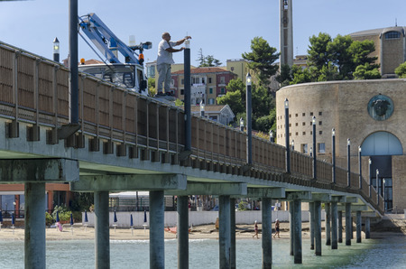 Francavilla al Mare, Italy - September 12, 2017: Worker changes bulb in precarious balance