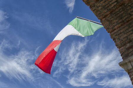 View of the Italian flag with clouds in the background Stock Photo