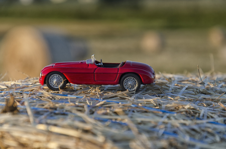View of a luxury auto on a straw round bale