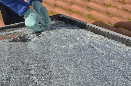 View of worker dismounting a damaged solar panel