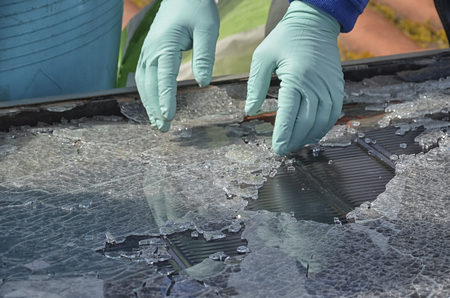 Technician collecting the glasses of a destroyed solar panel