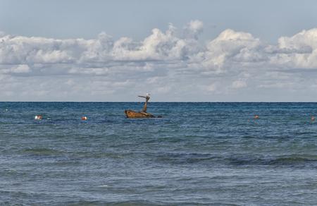 View of a rusty sunken boat near the beach