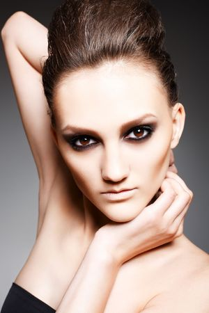 Fashion woman with dark evening smoky make-up in model pose Stock Photo