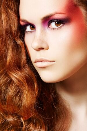 Attractive woman model with magic make-up and curly red hair photo