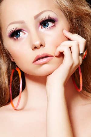 Fashion model with doll make-up, long eyelashes, big blue eyes photo