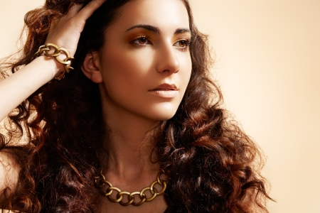 Glamour model with shiny gold jewelry, volume hair photo