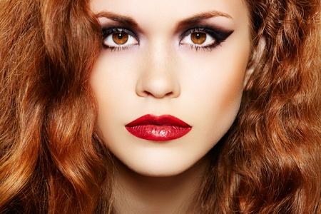 Beautiful woman model with luxury make-up and curly red hair photo