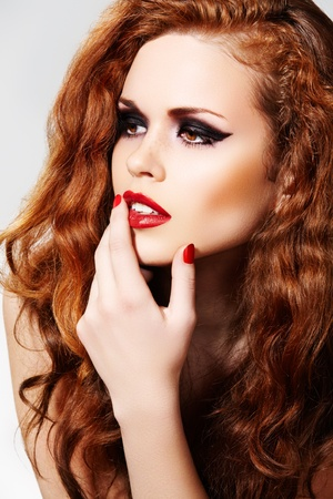 Chic woman model with luxury make-up and curly red hair photo