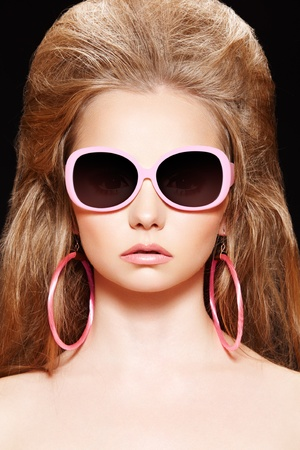 Doll style. Fashion model. Pink sunglasses, big hair, earrings Stock Photo - 9305270