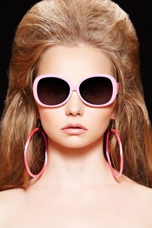 Doll style. Fashion model. Pink sunglasses, big hair, earrings photo