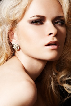 Luxury woman model with diamond earrings and blond hair photo