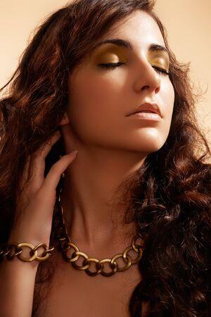 Fashion model with shiny gold jewellery, volume dark hair Stock Photo