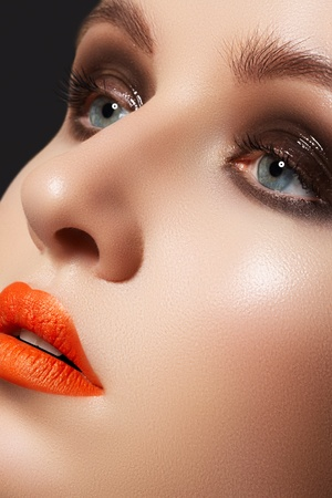 vibrance: Fashion model face with bright glamour makeup. Perfect skin, wet gloss eyeshadows on eyes and vibrance orange lipstick