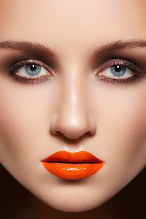 Glamourous woman face with fashion make-up. Sexy gloss makeup on lips, smoky-eye shadows, clean complexion  photo