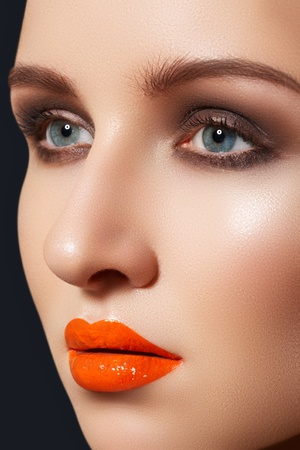 Cute woman model with bright fashion make-up. Sexy lip gloss makeup, dark shadows on eyelids, fresh clean complexion  Stock Photo