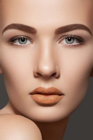 Spa, skincare, wellness & health. Close-up portrait of beautiful female model face with purity health skin, daily make-up. Perfect eyebrows, sexy light beige lips makeup.