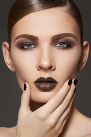 slicked: Fashion style, manicure, cosmetics and make-up. Dark lips makeup & nails polish. Close-up portrait of female model with brown lipstick, black fingernails and clean skin. Shiny slicked back hairstyle  Stock Photo