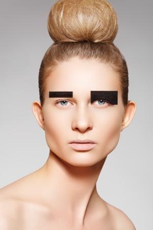 chignon: Fashion woman model with creative make-up, bun hairstyle with big chignon. Beautiful shiny volume hair
