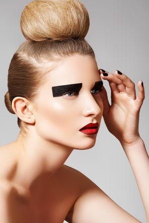 high fashion: High fashion style. Cosmetics and make-up. Beautiful woman model with perfect clean skin, creative black eye make-up, dark red lips and fashion bun hairstyle. Blond chignon bun on her head