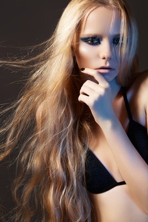 windswept: Beautiful young woman model with perfect long windswept hair, evening dark makeup. Sexy night fashion style