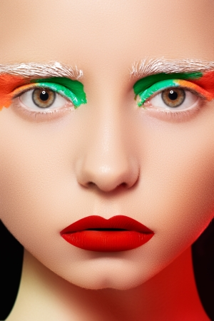 High fashion and beauty portrait photography. Beautiful girl model face with creative bright makeup like a doll, rainbow eyes and red lips make-up  photo