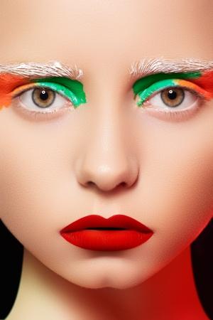 visage: La alta costura y la fotograf�a de retrato de belleza. La cara bella modelo chica con maquillaje creativo brillante, como una mu�eca, los ojos del arco iris y los labios rojos de maquillaje