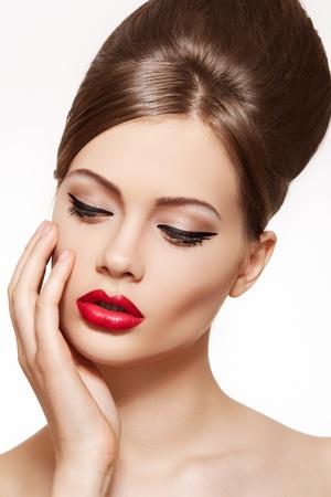 labios sensuales: Hermoso retrato de la sensual modelo europeo mujer joven con los labios rojos glamour maquillaje, maquillaje de flecha ojos, la piel pureza. Estilo de belleza retro Foto de archivo