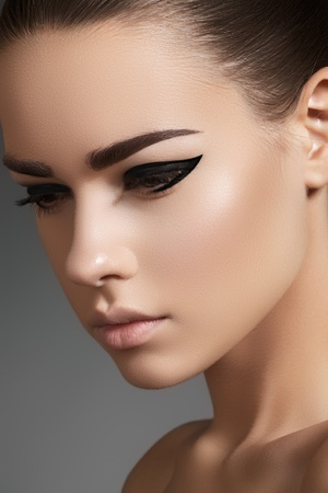 Glamourous closeup female portrait. Fashion evening elegance eyeliner makeup on model eyes. Cosmetics and make-up