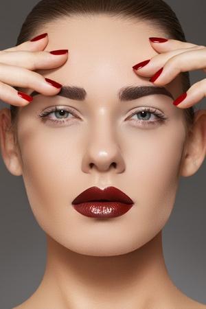 labios rojos: Casa de estilo de la moda, manicura, cosmética y maquillaje. Labios maquillaje oscuro y las uñas. Close-up retrato de la modelo femenina con lápiz labial rojo, las uñas y la piel limpia